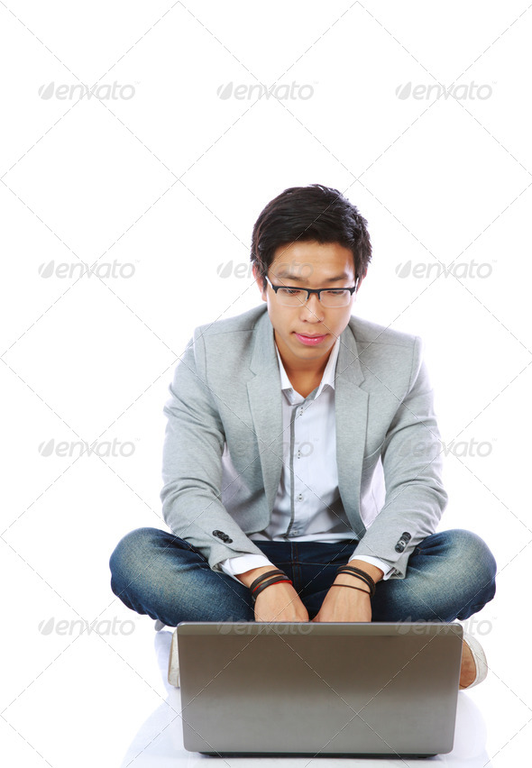 Young asian man sitting on the floor and using laptop over white background - Stock Photo - Images