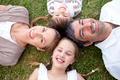 Happy family lying in a park - PhotoDune Item for Sale