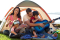 Happy family playing a guitar in a tent