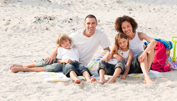 Family playing sitting on a beach - Stock Photo - Images