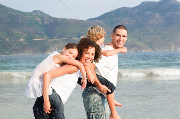 Happy family playing on the beach - Stock Photo - Images