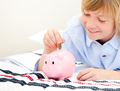 Cute boy putting a coin in a piggybank