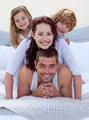 Portrait of happy family having fun in bed