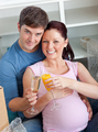 Happy couple expecting a baby drinking and sitting on the floor