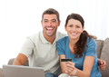 Cute couple with their laptop and credit card sitting in the liv - PhotoDune Item for Sale