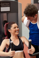 Joyful athletic woman using a shoulder press with her coach