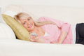 Attractive blonde female posing while lying on a sofa