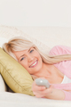 Beautiful blonde female posing while lying on a sofa