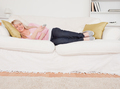 Attractive blonde female watching tv while lying on a sofa