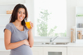 Beautiful pregnant woman drinking a glass of orange juice while
