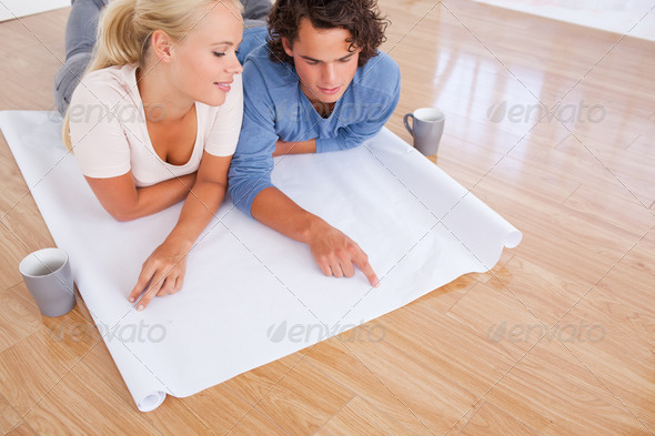 Young couple looking at their future room on a plan - Stock Photo - Images