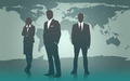 Businesspeople standing agsinst a map of the world