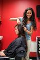 Portrait of a happy female hairdresser cutting hair