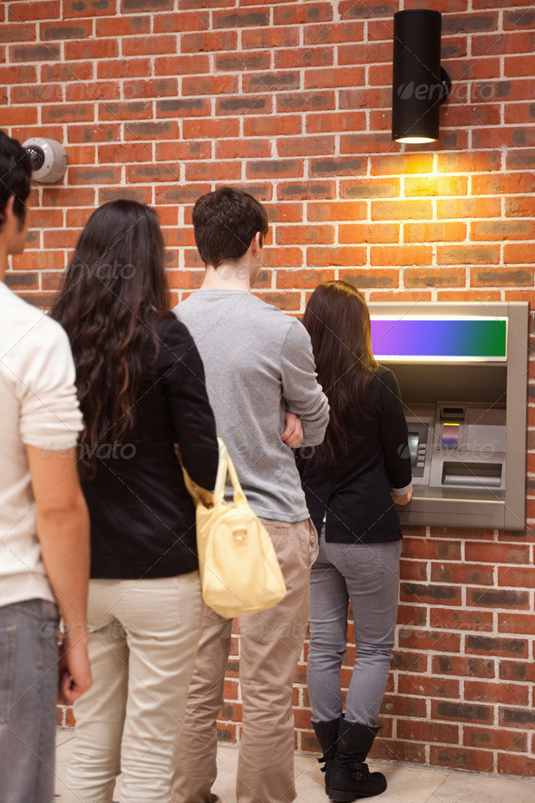 Portrait of people queuing to withdraw cash - Stock Photo - Images