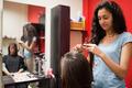 Female hairdresser cutting hair