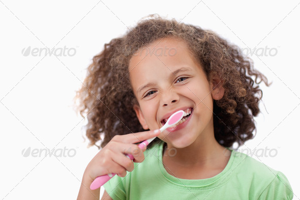 Smiling girl brushing her teeth - Stock Photo - Images