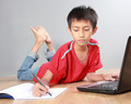 kid studying with books and laptop