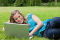 Young smiling girl lying on the side in a park while typing on her laptop - PhotoDune Item for Sale