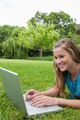 Young smiling girl using her laptop in a park while lying on the grass - PhotoDune Item for Sale