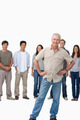 Mature man with hands on his hip and young people behind him - PhotoDune Item for Sale