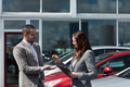 Businesswoman giving car keys to a client in a dealership - PhotoDune Item for Sale