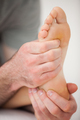 Hands of a practitioner holding a barefoot in a room - PhotoDune Item for Sale