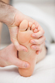 Foot being held by two hands in a medical room - PhotoDune Item for Sale