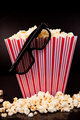 3D glasses hanging on a box full of popcorn against a black background - PhotoDune Item for Sale