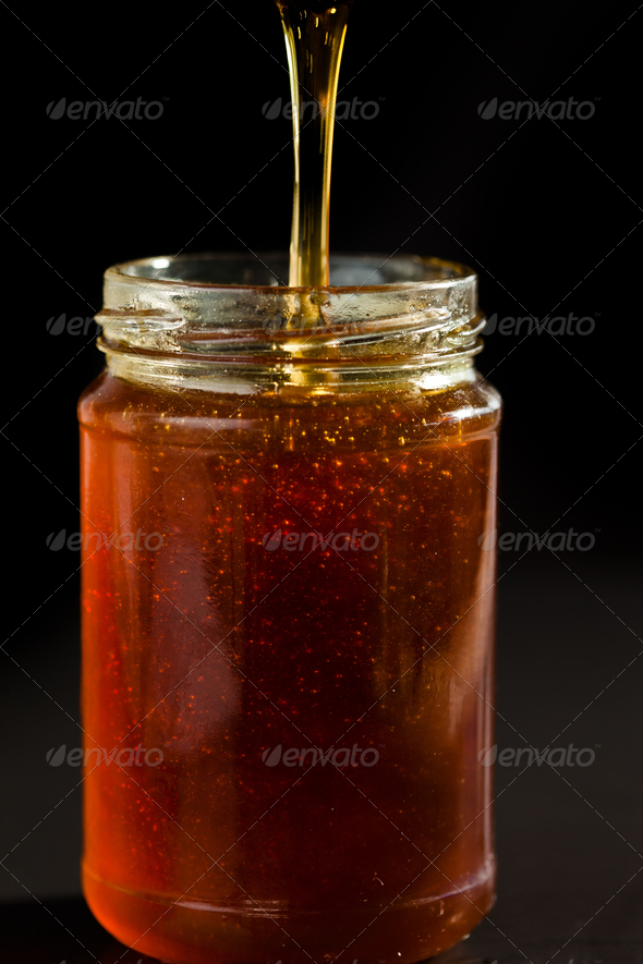 Honey trickle dropping in a honey jar against black background - Stock Photo - Images