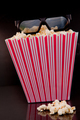 3D glasses on a box of pop corn against a black background - PhotoDune Item for Sale
