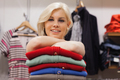 Woman leaning on clothes at a boutique smiling