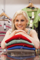 Woman is leaning on clothes in a boutique and smiling