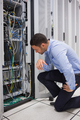 Technician looking at cables of the server in data center