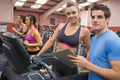 Gym Instructor and woman in the gym on the treadmill