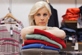 Woman is leaning on clothes in a boutique
