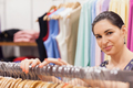 Woman standing by clothes rack in boutique