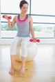 Woman lifting weights on exercise ball in fitness studio