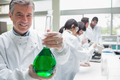 Chemist smiling and holding beaker of green liquid in lab - PhotoDune Item for Sale