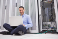 Smiling man sitting on floor checking servers with laptop in data center