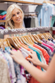 Woman standing at the clothes rack of a boutique smiling