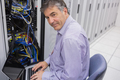 Man doing server  maintenance with notebook in data center and smiling