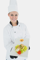 Portrait of young female chef offering healthy food over white background