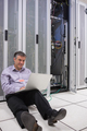 Smiling  technician working with his laptop near the server and sitting on floor of data server