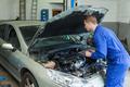 Male mechanic with digital tablet analyzing car engine
