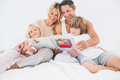 Smiling family reading a story together on a bed