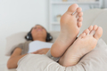 Woman with her feet up listening to music on the sofa - PhotoDune Item for Sale