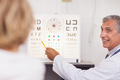 Doctor doing an eye test on a patient in a hospital examination room - PhotoDune Item for Sale
