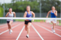 Female athletes racing towards finish line at track field - PhotoDune Item for Sale