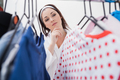 Young woman looking at clothing in closet