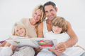 Happy family reading a fairy tale together on a bed